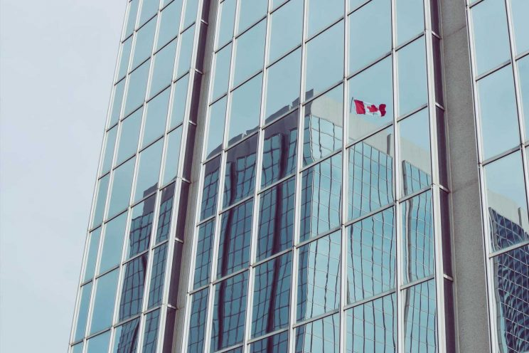 Canada flag reflected into a building window