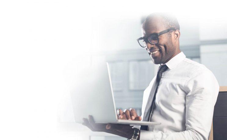 cheerful businessman holding laptop